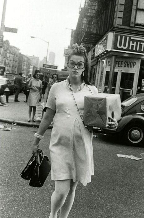 Модная женщина переходит дорогу с покупками.