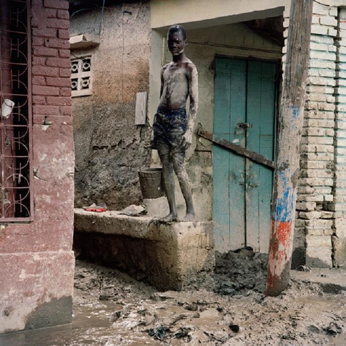 Мальчик убирает грязь из своего дома в центре города Гонаив. В 2008 году на Гаити обрушилось четыре урагана («Ханна», «Густав», «Айк» и «Фэй»), причинивших значительные разрушения. Река Ла-Кинта вышла из берегов и затопила город Гонаив, в результате чего погибли сотни людей. Из серии «Тонущий мир». Фотограф Gideon Mendel.
