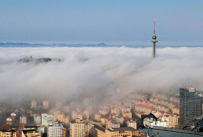 Туман клубится между жилыми зданиями города. Фото Reuters.