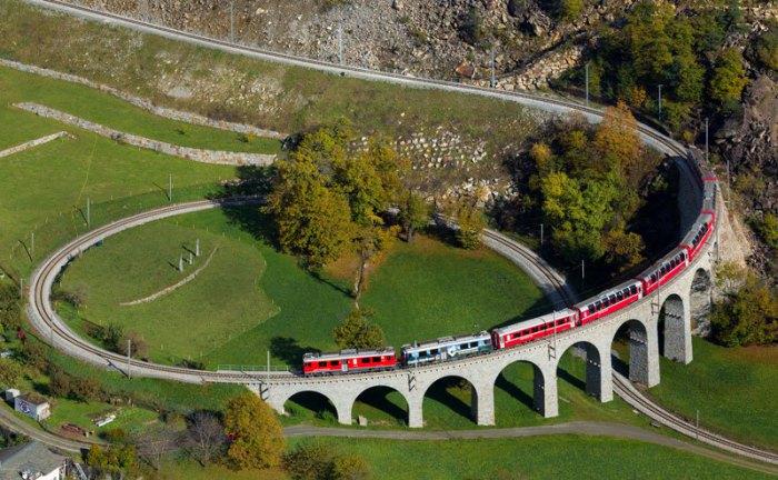 Ярко-красный экспресс мчится по извивающейся серпантином узкоколейной железной дороге.