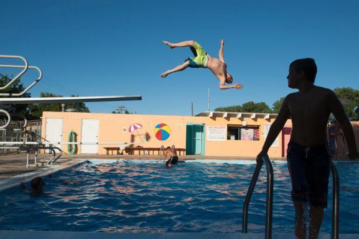Подросток прыгает в бассейн с трамплина в Крофтоне, штат Небраска.
