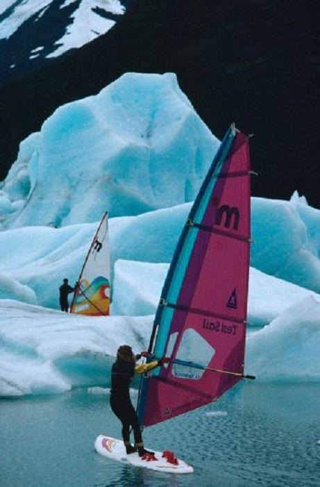 Пара занимается виндсёрфингом среди айсбергов на озере Портедж в штате Аляска.