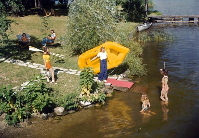 Девушка собирается спускать на воду надувную лодку.