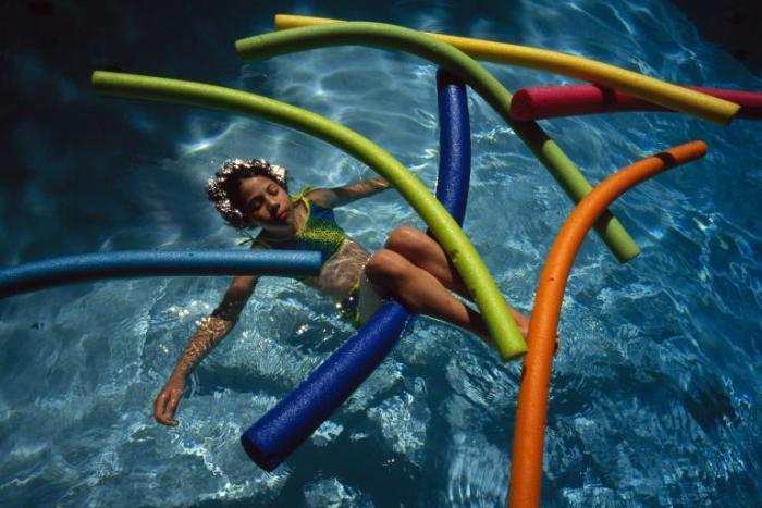 Девочка плавает и занимается гимнастикой в бассейне.