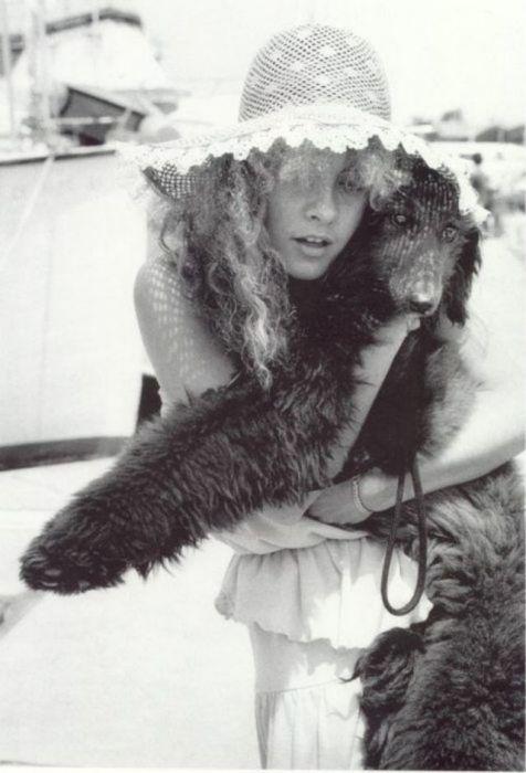 Молодая американская певица c своей собакой породы королевский пудель.