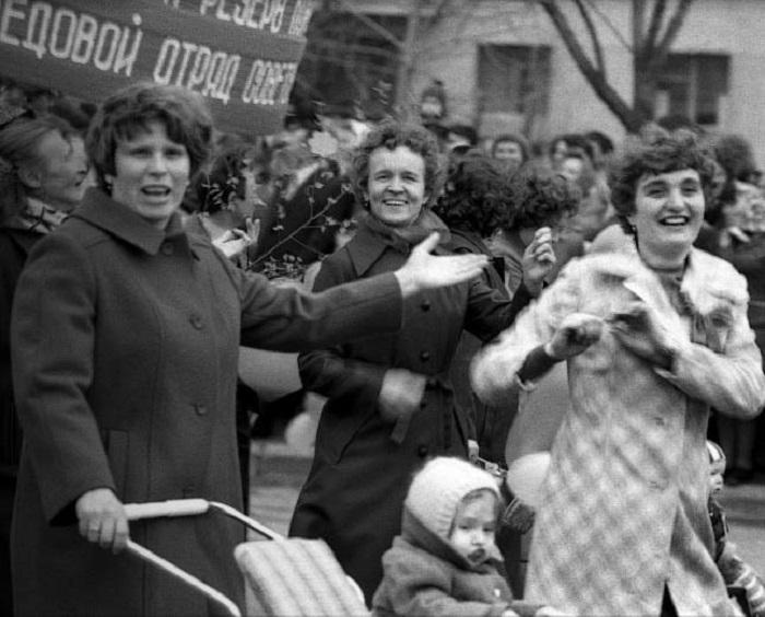 Нарядные женщины с детьми на массовом шествии.