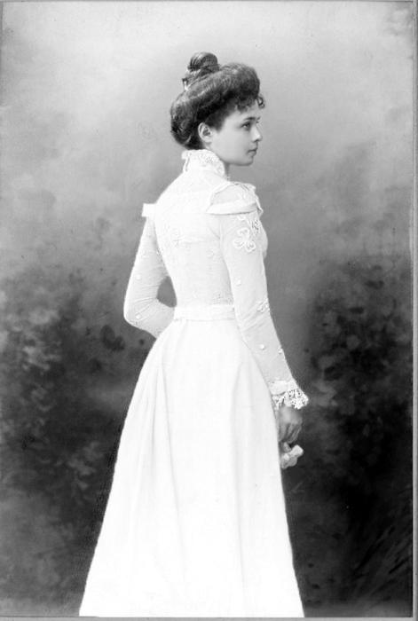 Женщина гуляет в саду в белом платье. 1900-е года.
