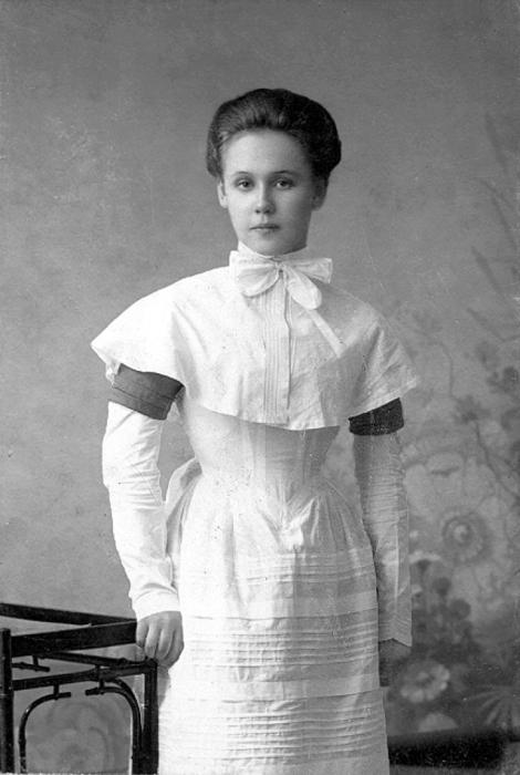 Выпускница в белой форме, получившая образование.