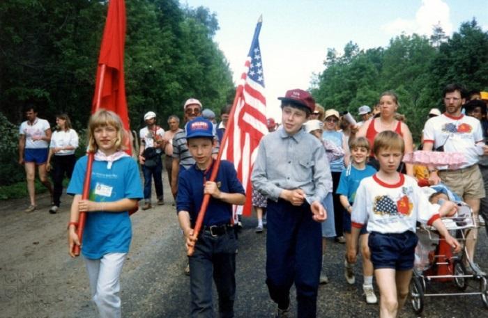 Советский мальчик с звездно-полосатым флагом США и американская девочка с советским флагом во время шествия из Москвы в Ленинград в 1987 году.