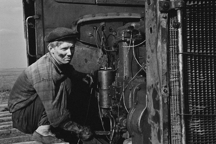 Мужчина ремонтирует свой трактор.