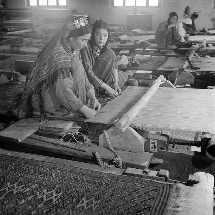 Девушки ткут полотна на ткацких станках.