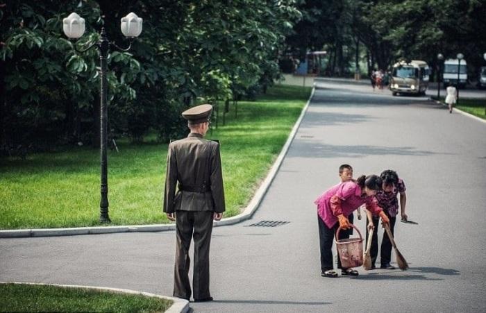 Уборщицы наводят порядок в парке Пхеньяна под бдительным контролем.
