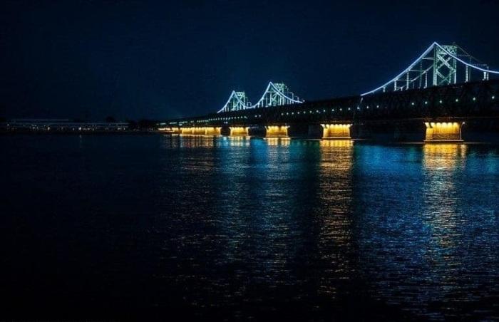 Освещенный мост с китайской стороны и погруженный во тьму на берегу Северной Кореи.