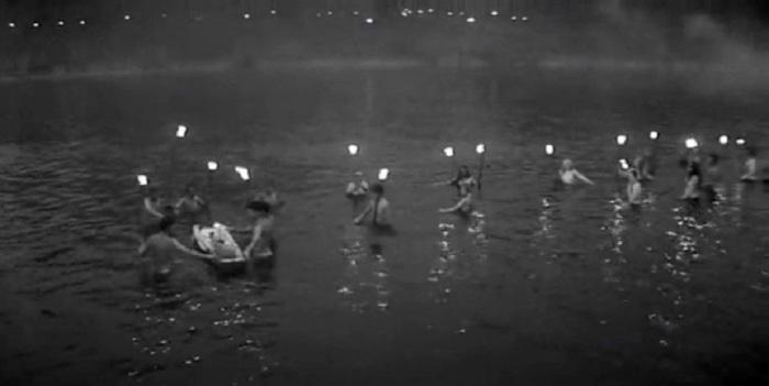 Обнаженные девушки и юноши ночью купаются в реке.