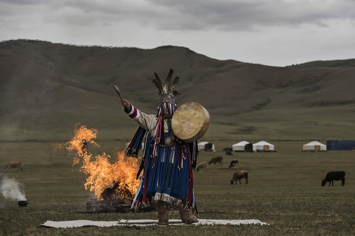 Шаман проводит огненный ритуал посреди огромного луга.