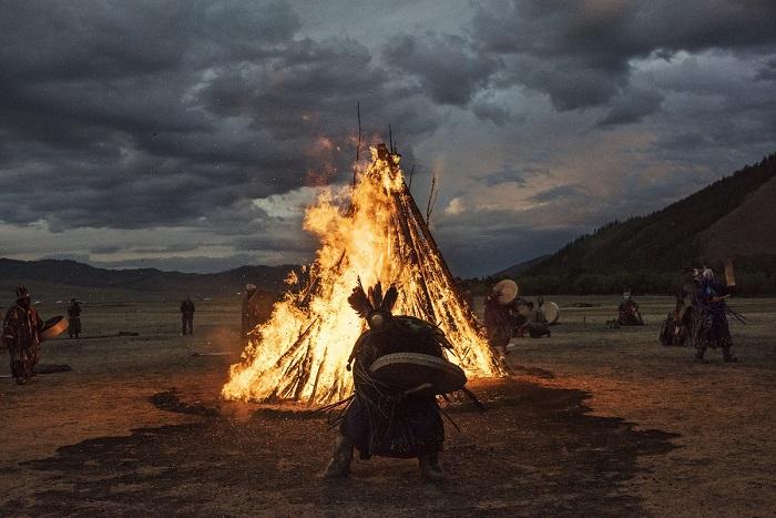 Ритуальный обрядовый танец шамана с бубном у огромного костра.