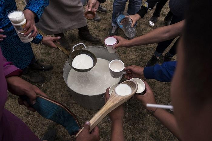 Шаманы разливают молоко, чтобы преподнести его в качестве подношения почитаемым духам.