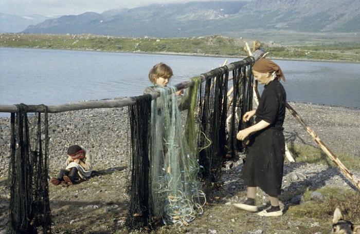 Женщина и две девочки приводят в порядок рыболовецкое снаряжение.