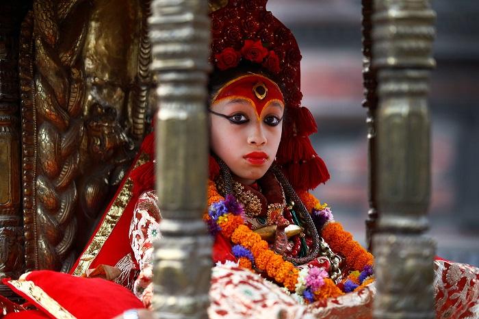 Богиня Кумари с огненным глазом на лбу одета в красные одежды.