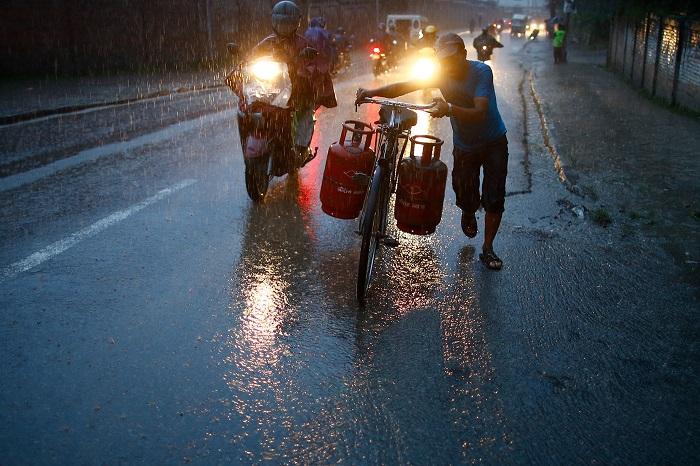 Непалец под проливным дождем перевозит на велосипеде баллоны.