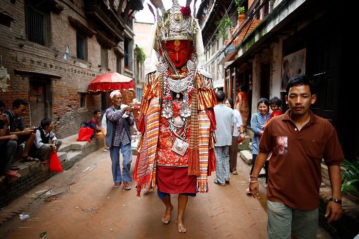 Непальский мужчина переодет в костюм Будды Дипанкара проходит по улицам.