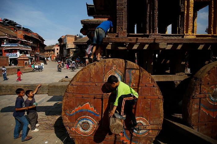Ребята рассматривают колесницы, на которых перевозят изображения бога Бхайравы и богини Бхадракали.