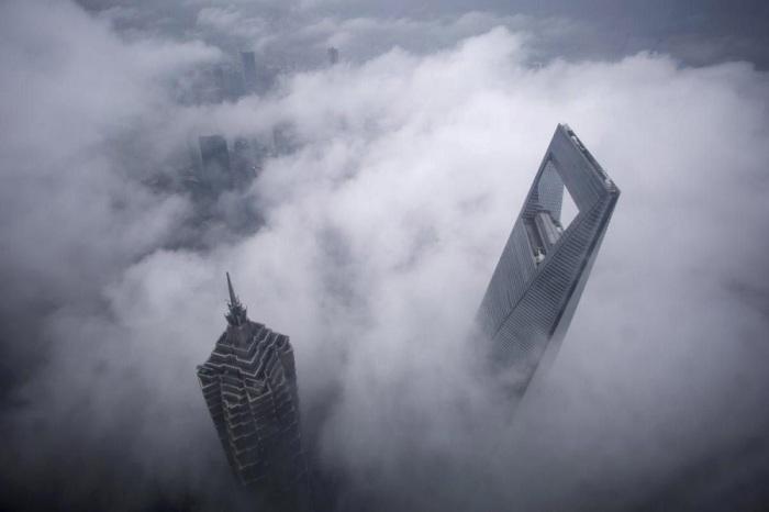 Туман клубится между самыми высокими зданиями города. Фотограф Али Сонг (Aly Song).