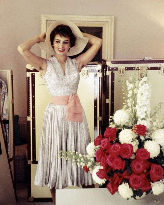 Софи Лорен в серебристом платье без рукавов с широким розовым поясом.