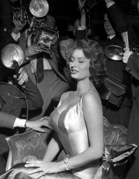 Актриса в облегающем шелковом платье под прицелом объективов фотографов.