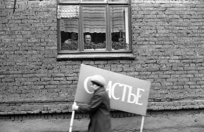 Женщина с плакатом спешит на первомайскую демонстрацию. Новокузнецк.