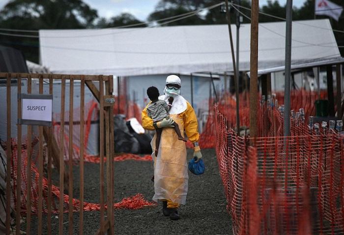 Медработник в защитной одежде несет ребенка с подозрением на вирус Эбола, Либерия.