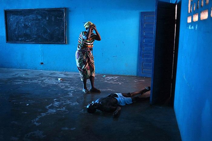 Заразившийся вирусом Эбола муж упал без сознания, жена стоит рядом. Монровия, Либерия.