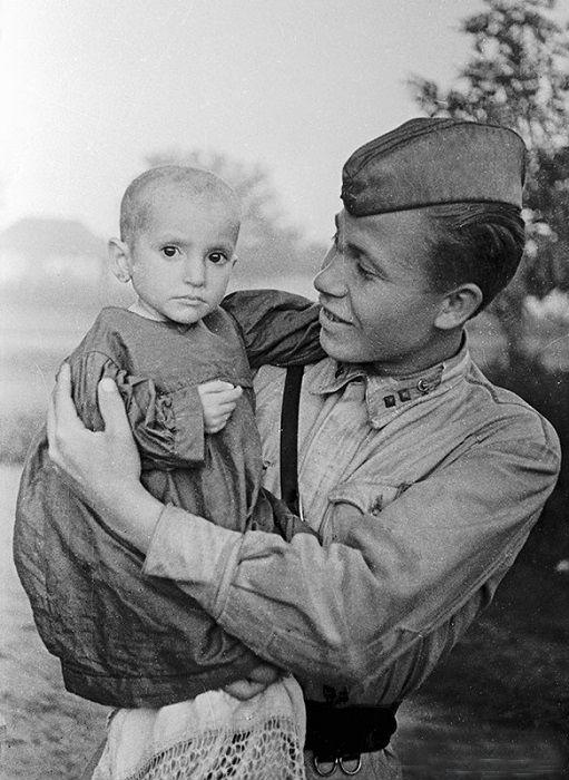 Советский офицер держит на руках спасенную им девочку из деревни Эльхотово, 1942 год.