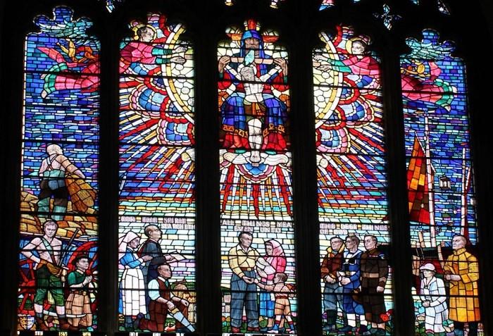 На широких окнах с западной стороны изображены яркие витражные рисунки с изображением Британских святых.