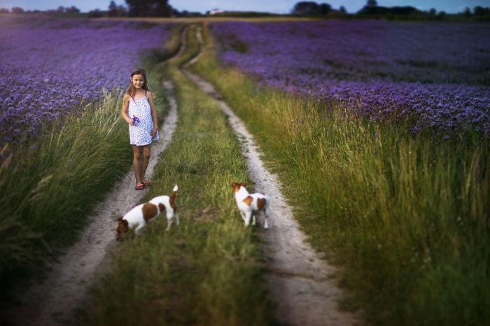 Девочка с веселыми спутниками между фиолетовых полей.