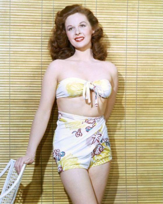 Американская модель и киноактриса позирует в портретной студии в купальном костюме с летним принтом.