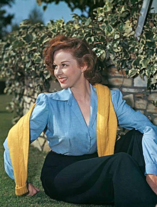 Начинающая актриса и модель позирует для женского журнала в голубой блузе и желтом свитере, накинутом на плечи.