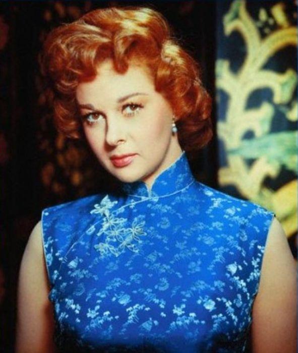 Обладательница престижной кинопремии «Оскар» позирует фотографу в расписной голубой блузе из шелка.