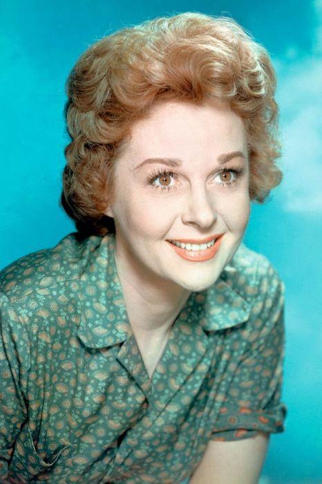 Студийный портретный снимок рыжеволосой актрисы Сьюзен Хэйворд на фоне голубого неба и облаков.