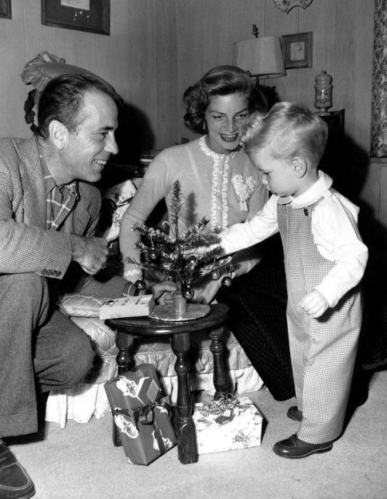 Американский киноактер Хамфри Богарт (Humphrey Bogart) вместе с женой Лорен Бэколли и сыном Стивеном украшают рождественскую елочку.