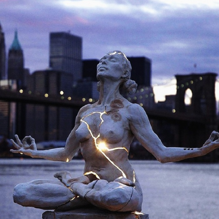 Скульптура «Расширение» представляет собой двухметровую композицию из светящегося постамента, на котором в позе лотоса восседает обнаженная женщина.