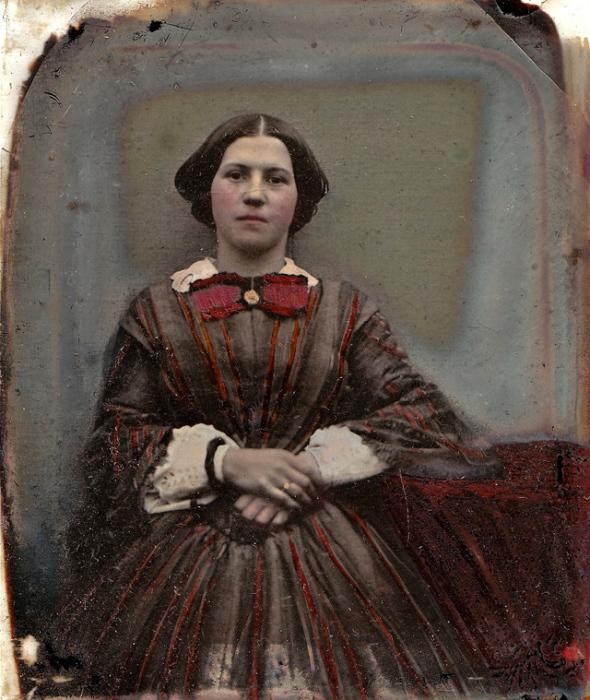 Платье тёмного цвета с бардовыми полосами и бантом-брошью.