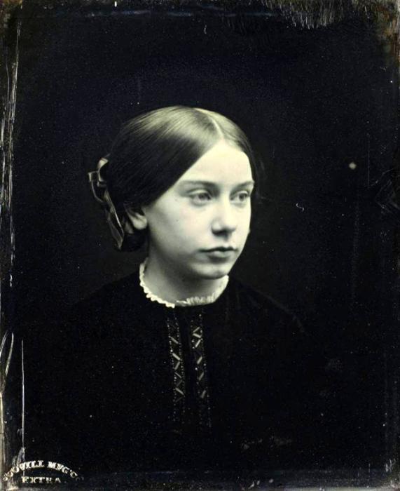 Девушка в скромном чёрном платье с легкой вышивкой.