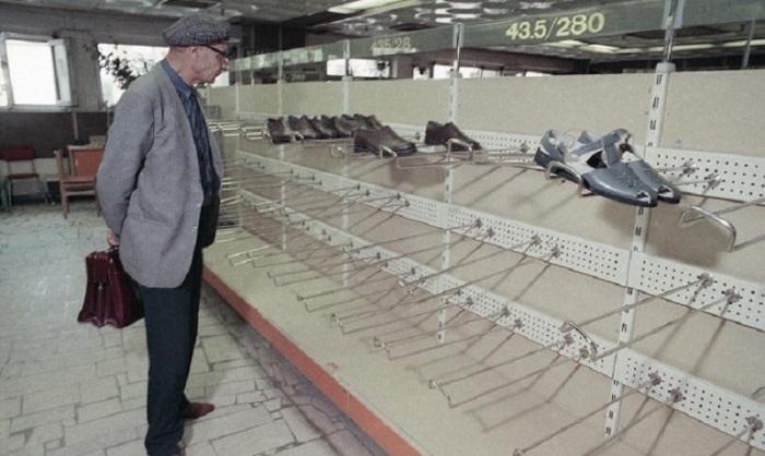 Мужчина разглядывает опустевшие полки обувного отдела в универмаге «Московский», 1990 год.