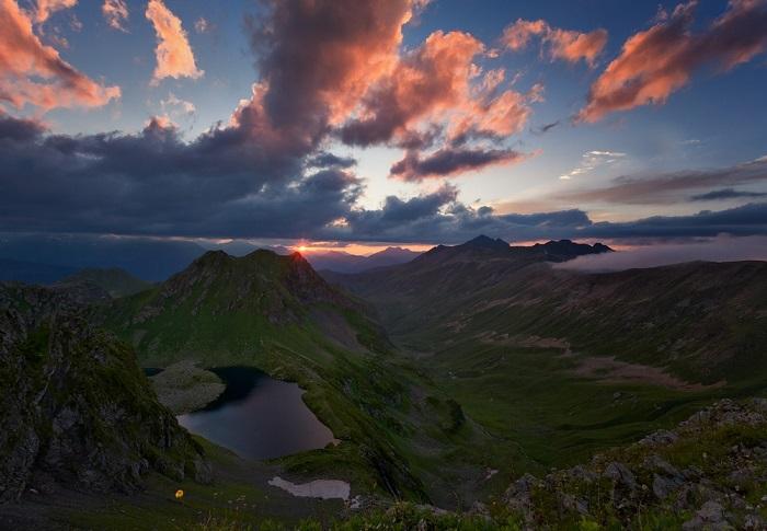 Спокойная поверхность красивого озера, окруженная скалами и осыпями, отражает плывущие в небе облака, которые окрашены лучами заходящего солнца.