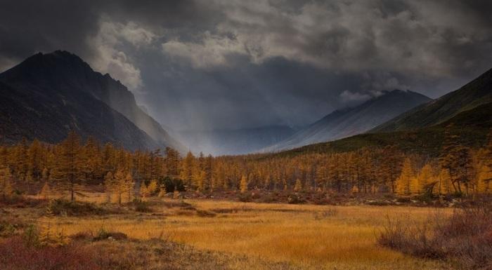 Золотой осенний горный пейзаж во время грозы.