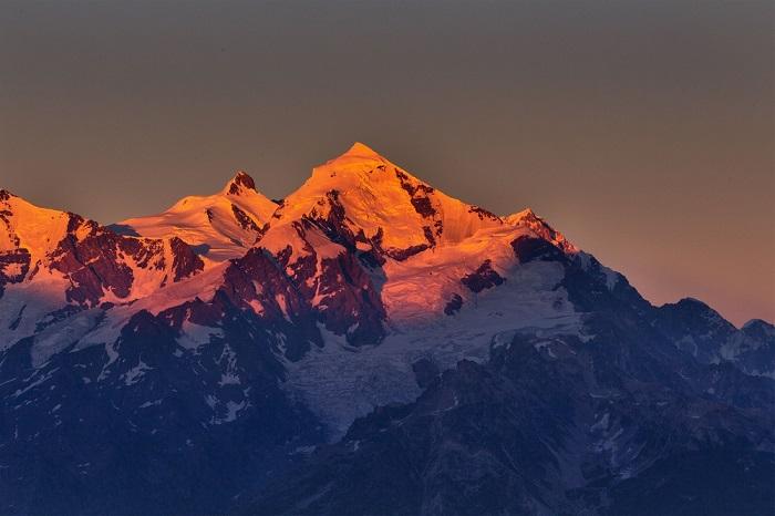 Окрашенные лучами восходящего солнца ледники на вершине гор очень напоминают расплавленное золото.