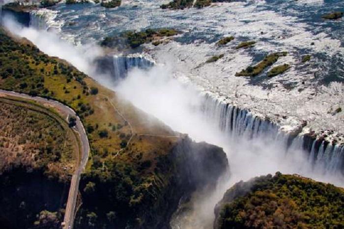 """Легендарная достопримечательность, которую местные жители называют «Моси-оа-Тунья» («гремящий дым»""""), привлекает туристов со всех концов света - могучая река Замбези спадает вниз, образуя водяной занавес протяженностью почти 2 километра."""