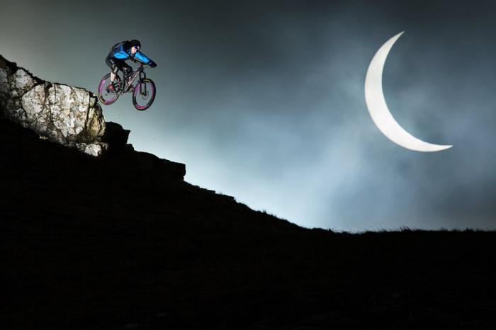 Дэнни МакАскилл (Danny MacAskill) исполняет трюк на велосипеде во время солнечного затмения.
