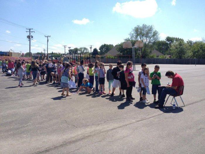 Ученики начальной школы выстроились в очередь, чтобы подписать выпускной альбом у школьного уборщика.